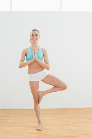 Smiling slim blonde standing in eagle pose in bright room photo