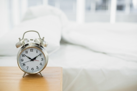 'bedside table': Retro alarm clock standing on a bedside table in a bedroom