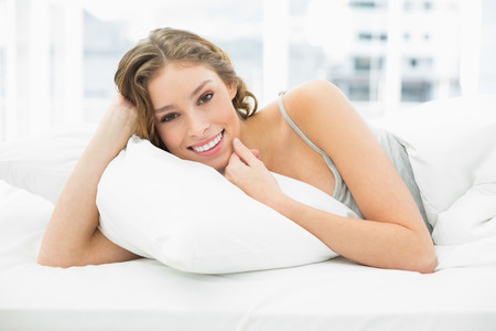 Peaceful content woman lying in her bed under the cover smiling at camera photo