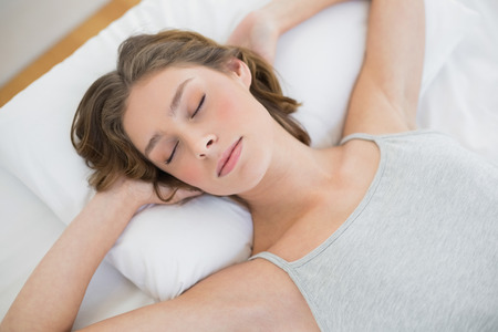 peacefully: Peacefully sleeping woman lying on her white bed in the bedroom