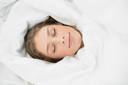 hair wrapped up: Beautiful woman lying sleeping under the cover on her bed in the bedroom