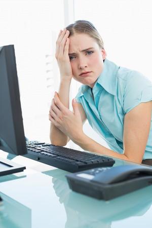 Classy upset businesswoman having a headache in bright office