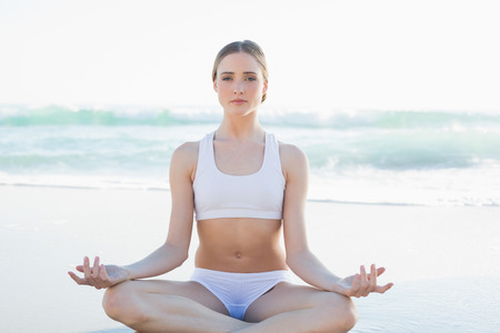 Gorgeous young woman meditating sitting on the beach looking at camera photo