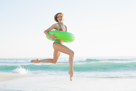 Gorgeous young woman holding a rubber ring while jumping on beach and looking at camera photo