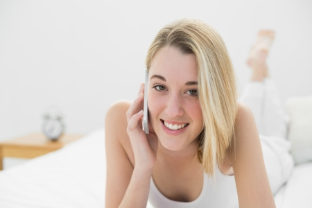 gleeful: Gleeful young woman smiling at camera while phoning with her smartphone lying on her bed