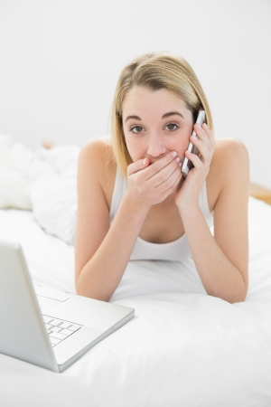 Portrait of attractive surprised woman phoning lying on her bed next to her laptop photo