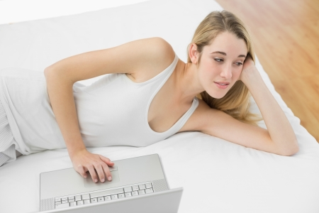 Thoughtful calm woman using her notebook lying on her bed at home photo