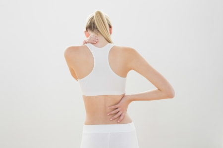 Slender sporty woman touching her injured nape wearing sportswear photo