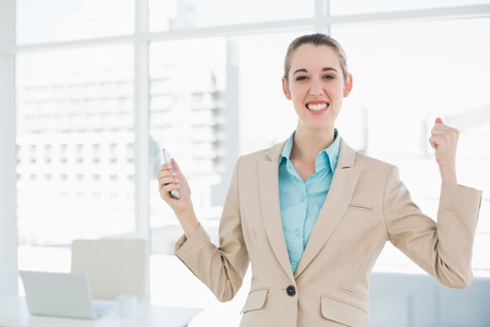 Attractive cheerful businesswoman holding her smartphone smiling at camera photo