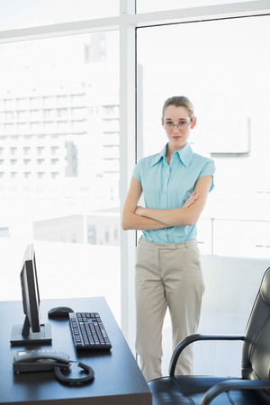 Calm serious businesswoman posing with arms crossed standing in her office looking at camera photo