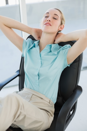 Tired chic businesswoman relaxing sitting on her swivel chair with eyes closed photo
