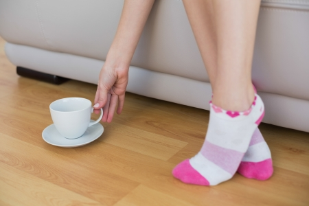Slender woman wearing pink socks reaching for a cup sitting on couch Stock Photo - 25426589