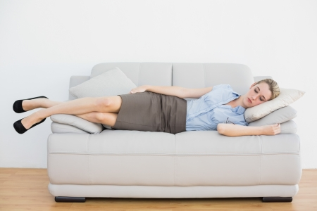 Peaceful blonde chic businesswoman lying sleeping on couch in the office Stok Fotoğraf