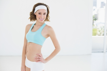 Attractive slender woman wearing sportswear posing in sports hall smiling at camera photo