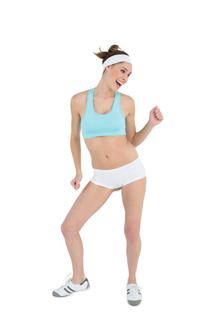 Happy ponytailed woman dancing wearing sportswear on white background photo
