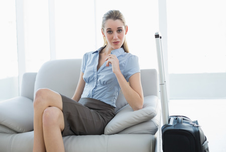 Chic businesswoman posing sitting on couch nest to her suitcase looking at camera photo