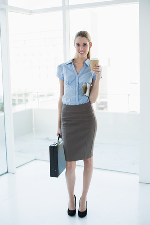 Young classy businesswoman posing holding a briefcase and newspaper and a disposable cup photo