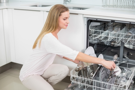 Calm gorgeous model kneeling next to dish washer in bright kitchen