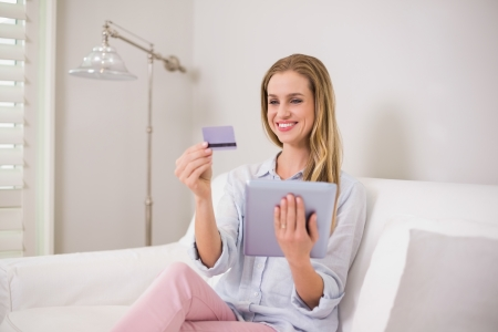 Happy casual blonde using tablet for online shopping in bright living room photo