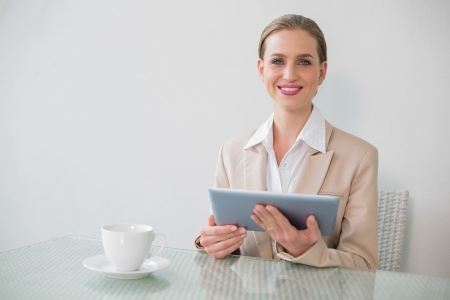 Lucky stylish businesswoman using tablet in bright office photo