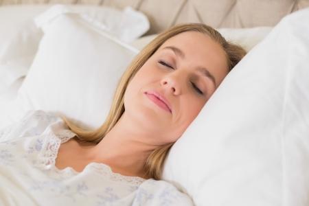 slumbering: Natural content woman slumbering in bed in bright bedroom