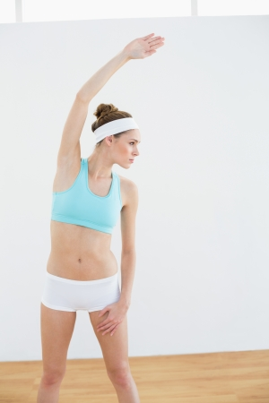 Concentrated slender woman stretching her body in sports hall photo