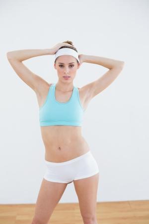 salle de sport: Attractive femme mince posant dans des v�tements de sport en regardant la cam�ra dans la salle de sport