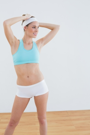Happy sporty woman wearing sportswear posing lifting her arms in sports hall photo