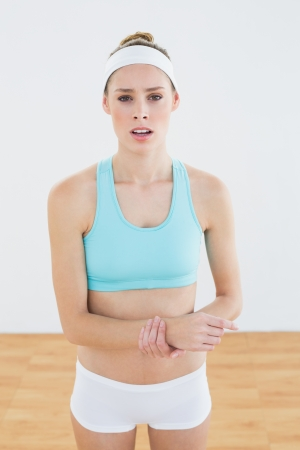 Young slim woman in sportswear touching her injured wrist looking at camera