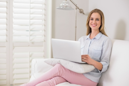 Gleeful casual blonde sitting on couch using laptop in bright living room photo