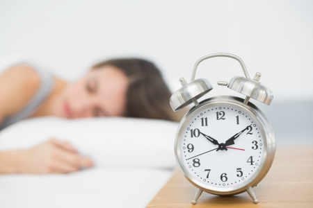 Retro alarm clock standing on bedside table with sleeping woman in background photo