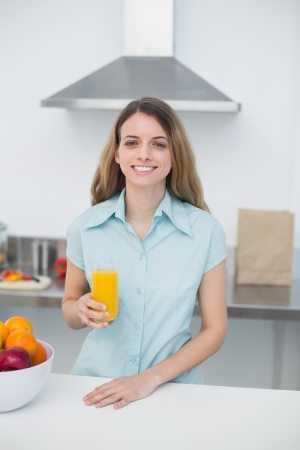 Beautiful brunette woman posing standing in kitchen holding a glass of orange juice smiling at camera photo
