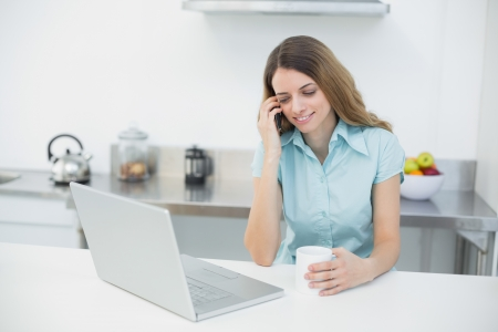 Amused gorgeous woman using her notebook while holding a cup and standing in her kitchen photo