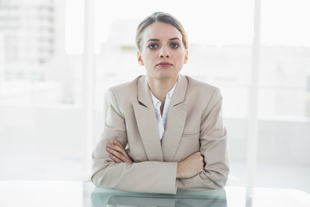 unsmiling: Concentrated blonde businesswoman looking at camera sitting at her desk