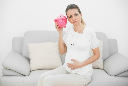 Disappointed pregnant woman shaking a pink piggy bank while holding her belly and looking at camera photo