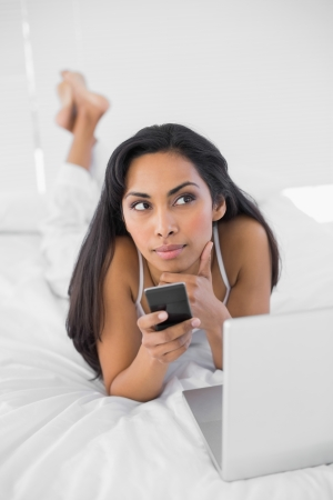 Natural thinking woman holding her smartphone lying on her bed photo