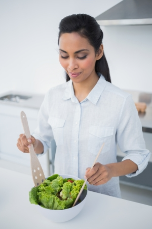 Lovely peaceful woman preparing salad in kitchen at home photo