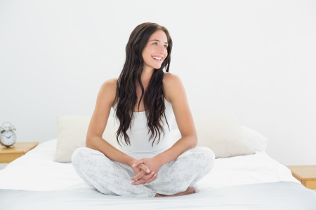 Smiling young woman sitting in bed and looks away photo