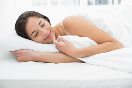 sleep well: Pretty young woman sleeping in bed with eyes closed