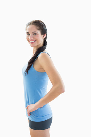 Side view portrait of a slim smiling young woman in sportswear over white background photo