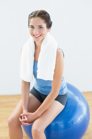 Portrait of a smiling young woman with towel around neck sitting on exercise ball photo
