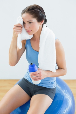 Tired young woman with towel around neck and waterbottle sitting on exercise ball photo