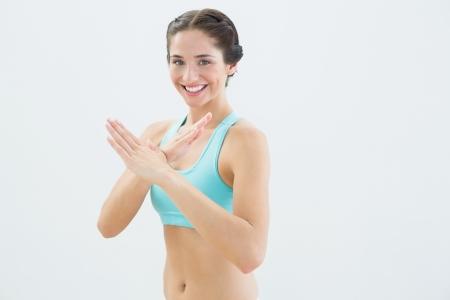 defensive posture: Retrato de una mujer joven en forma sonriente de pie en la defensa de la postura contra el fondo blanco