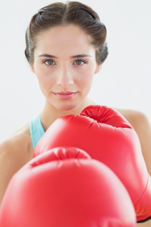 Close-up portrait of a beautiful young woman in red boxing gloves over white background photo