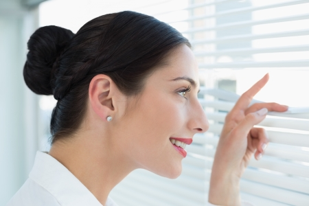 side by side: Close-up side view of a smiling young business woman peeking through blinds at office Stock Photo