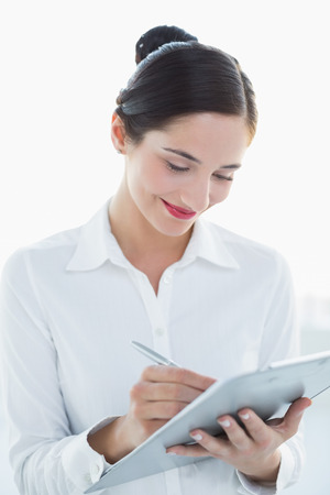 tied down: Smiling young business woman with clipboard and pen over white background