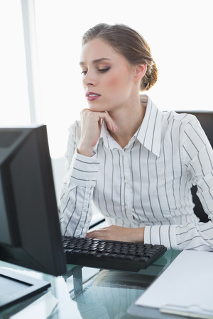 swivel: Young serious businesswoman sitting at her desk in the office Stock Photo