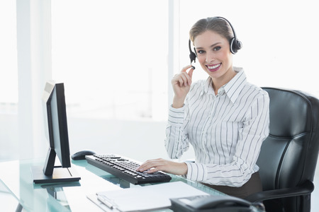 swivel: Gorgeous chic agent wearing headset sitting at her desk smiling at camera