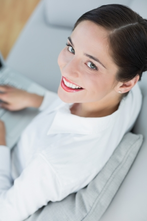 High angle view of a smiling well dressed young woman using laptop on sofa at home photo