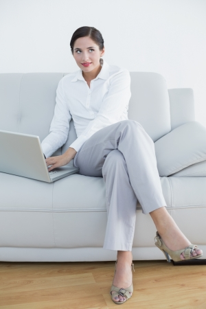 Well dressed young woman using laptop while looking up at home photo